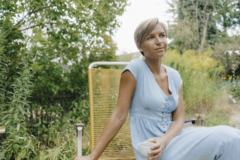 Woman sitting in garden with cup of coffee - KNSF05061