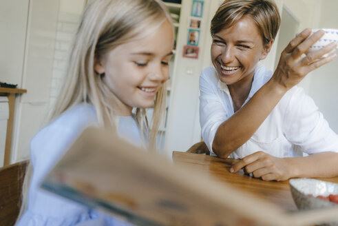 Happy mother and daughter with book sitting at table at home - KNSF05073