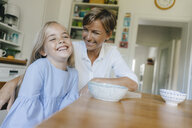 Happy mother and daughter sitting at kitchen table at home - KNSF05079