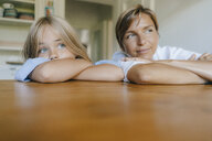 Mother and daughter leaning on kitchen table at home - KNSF05085