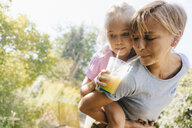 Mother carrying daughter piggyback in garden drinking a smoothie - KNSF05097