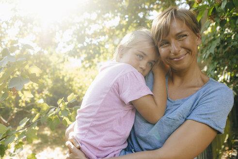 Happy mother carrying daughter in garden - KNSF05103