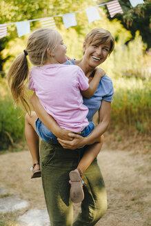 Happy mother carrying daughter in garden - KNSF05109