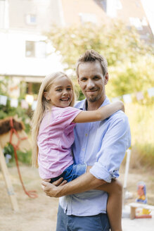 Portrait of smiling father carrying daughter in garden - KNSF05121