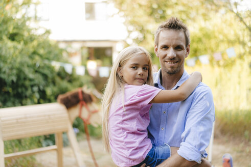 Portrait of smiling father carrying daughter in garden - KNSF05124