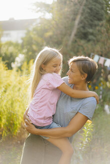 Smiling mother carrying daughter in nature - KNSF05130