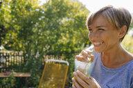 Happy woman drinking a sof drink in garden - KNSF05136