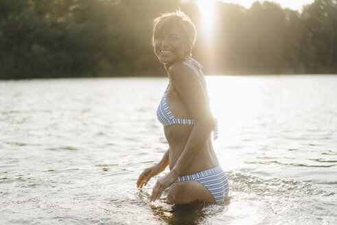 Portrait of happy woman wearing a bikini in a lake - KNSF05154