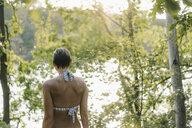 Rear view of woman wearing a bikini at a lake - KNSF05175