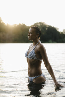 Woman wearing a bikini in a lake at sunset - KNSF05187