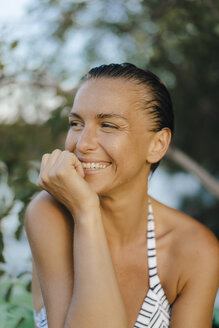 Portrait of happy woman with wet hair wearing a bikini at a lake - KNSF05190