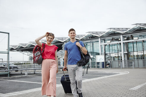 Smiling couple walking outside airport - RHF02205