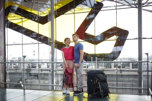 Smiling couple standing at the airport - RHF02214