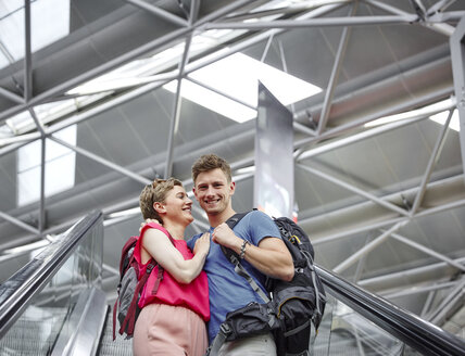 Happy couple on escalator at the airport - RHF02217
