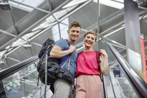 Happy couple on escalator at the airport - RHF02220