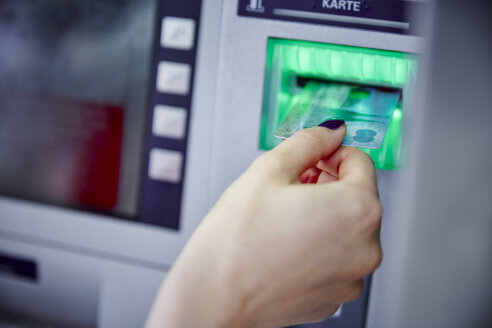 Close-up of woman putting card into slot of cash machine - RHF02229