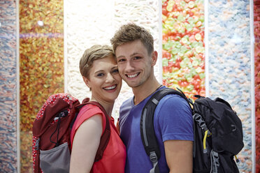 Portrait of happy couple with backpacks at multicoloured wall - RHF02235