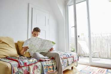 Young man sitting on couch at home reading map - RHF02265