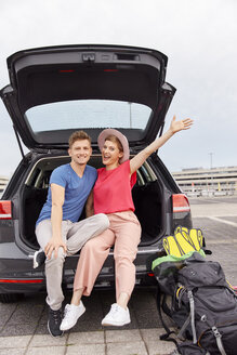 Portrait of happy young couple in a car at the airport - RHF02268