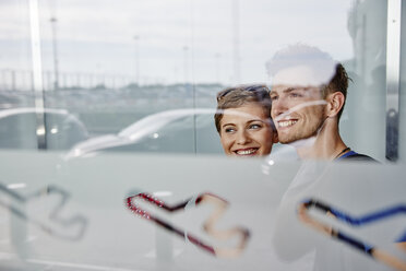 Portrait of smiling couple at the airport looking out of window - RHF02280