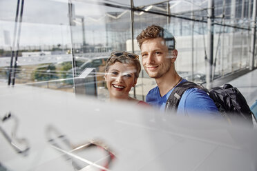 Portrait of smiling couple at the airport looking out of window - RHF02289