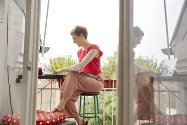 Happy woman sitting on balcony at home with laptop and map - RHF02292