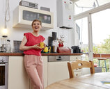 Happy woman having a coffee break in kitchen - RHF02298