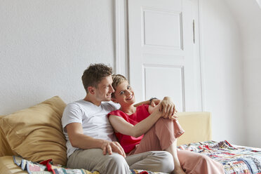 Happy relaxed couple sitting on couch at home - RHF02301