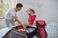 Happy couple packing suitcase for summer vacation on bed - RHF02307