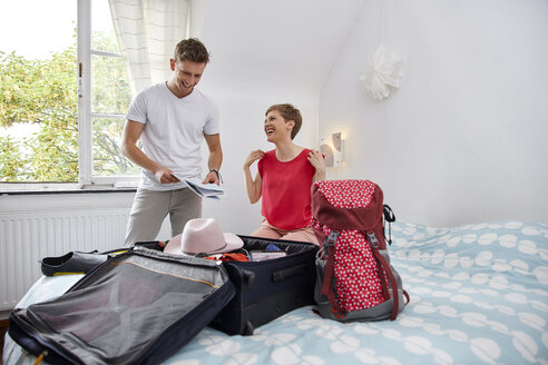 Happy couple packing suitcase for summer vacation on bed - RHF02310
