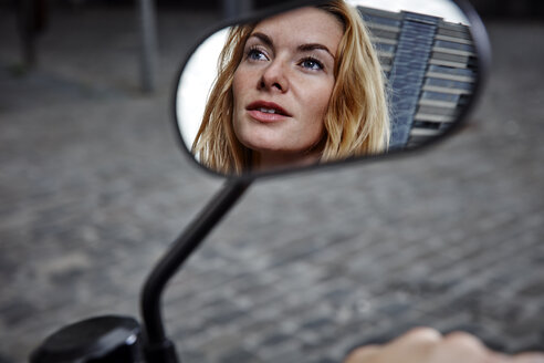 Portrait of confident young woman reflected in wing mirror of a motorcycle - RHF02313