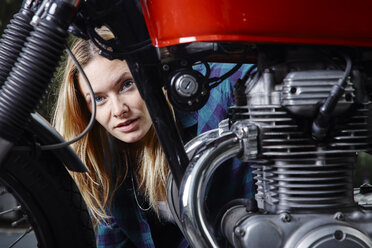 Portrait of confident young woman behind motorcycle - RHF02316