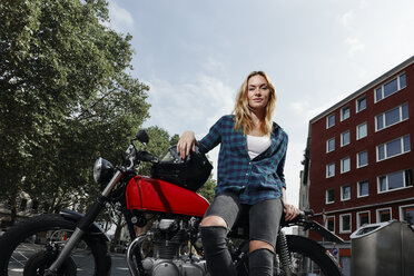 Portrait of confident young woman with motorcycle - RHF02319