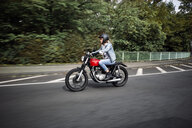 Young woman riding motorcycle on a street - RHF02322