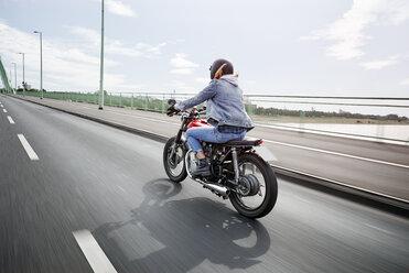 Young woman riding motorcycle on bridge - RHF02325