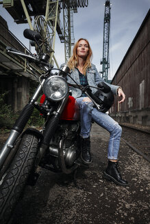 Portrait of confident young woman on motorcycle - RHF02328