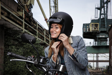 Smiling young woman putting on motorcycle helmet - RHF02334