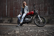 Laughing young woman with motorcycle - RHF02337