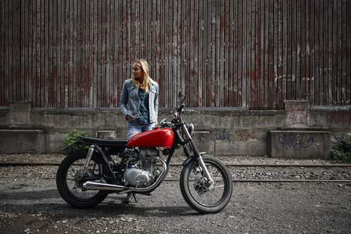 Young woman standing next to motorcycle looking away - RHF02340