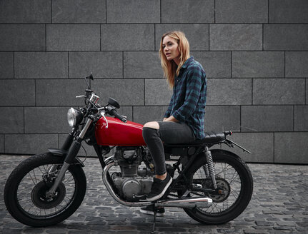 Confident young woman on motorcycle - RHF02346