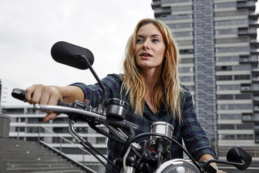 Portrait of confident young woman on motorcycle - RHF02349