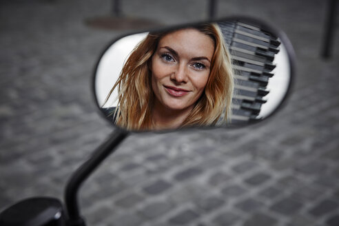 Portrait of smiling young woman reflected in wing mirror of a motorcycle - RHF02352