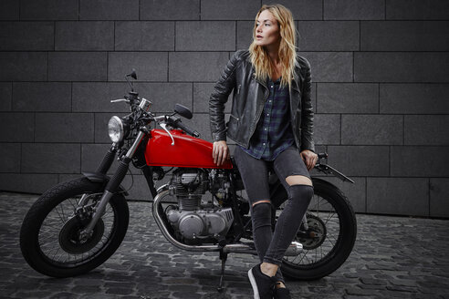 Confident young woman with motorcycle looking away - RHF02355