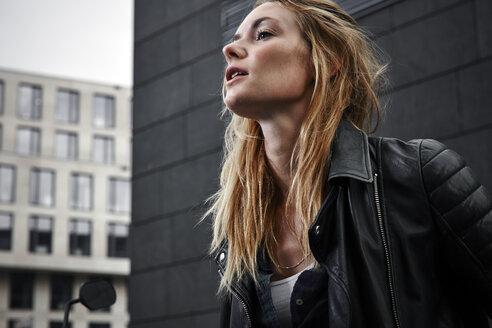 Confident young woman wearing biker jacket looking away - RHF02361