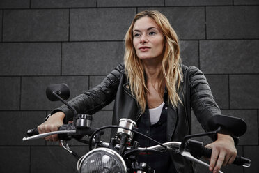Portrait of confident young woman on motorcycle - RHF02364