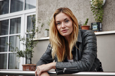 Portrait of confident young woman wearing biker jacket leaning on balcony railing - RHF02367