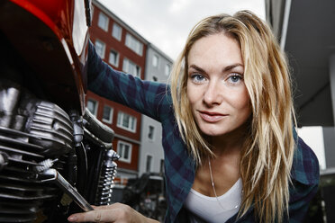 Portrait of confident young woman working on motorcycle - RHF02373