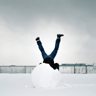 Low angle view of a man upside down on a snowball under grey skies - INGF04225