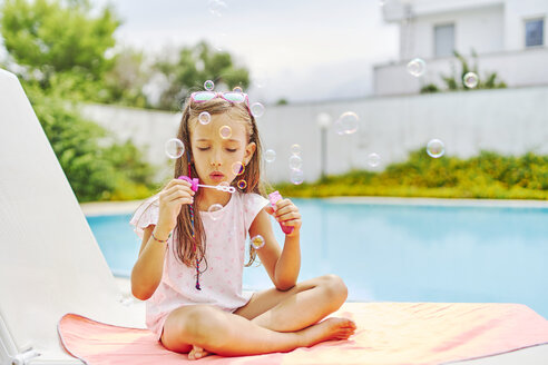 Girl blowing soap bubbles at the poolside - DIKF00304