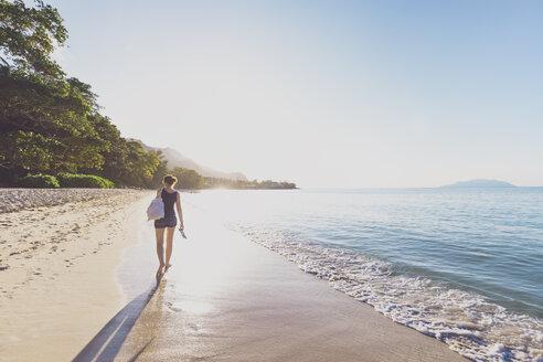 Seychelles, Mahe, Beau Vallon Beach, woman walking on the beach at sunset - MMAF00683